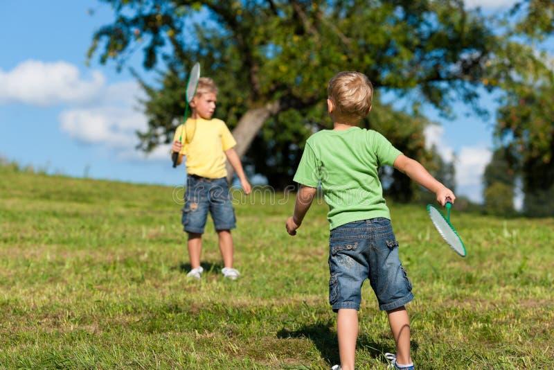 Família - dois rapazes pequenos que jogam o badminton ao ar livre