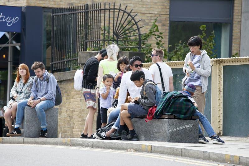 Família dos asiáticos que sentam-se em um banco perto do mercado de Broadway que come o almoço imagem de stock royalty free