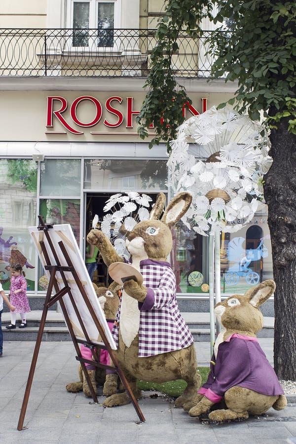 A família dos coelhos brinca perto da loja Roshen em Lviv, Ucrânia imagens de stock royalty free