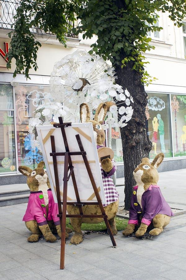 A família dos coelhos brinca perto da loja Roshen em Lviv, Ucrânia imagens de stock