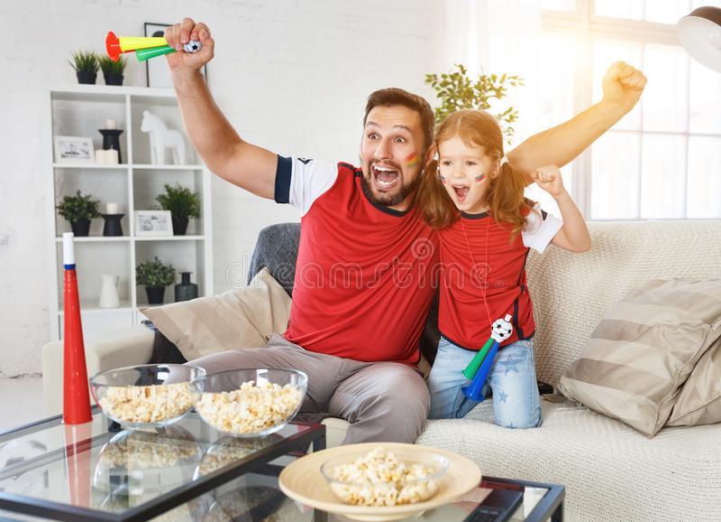 Família dos fãs que olham um fósforo de futebol na tevê em casa foto de stock