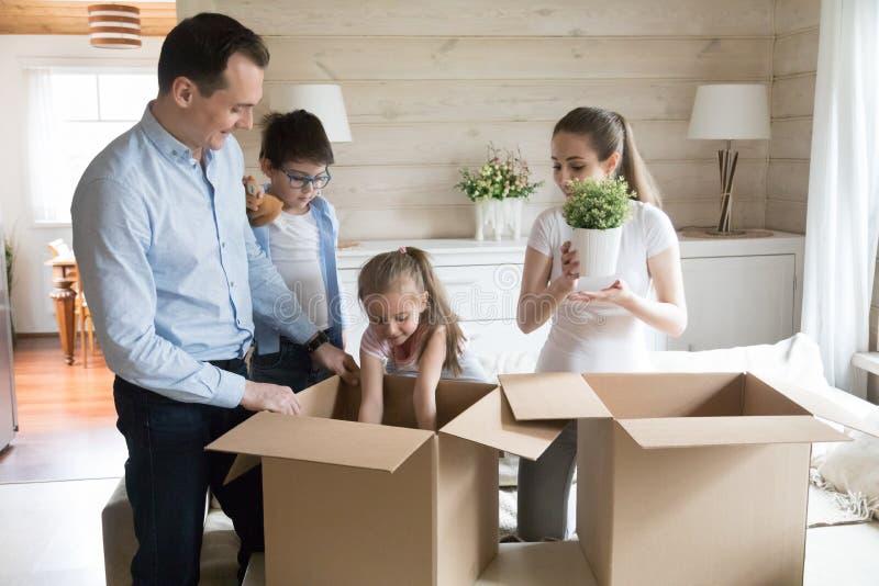 A família e as crianças desembalam seus pertences imagens de stock royalty free