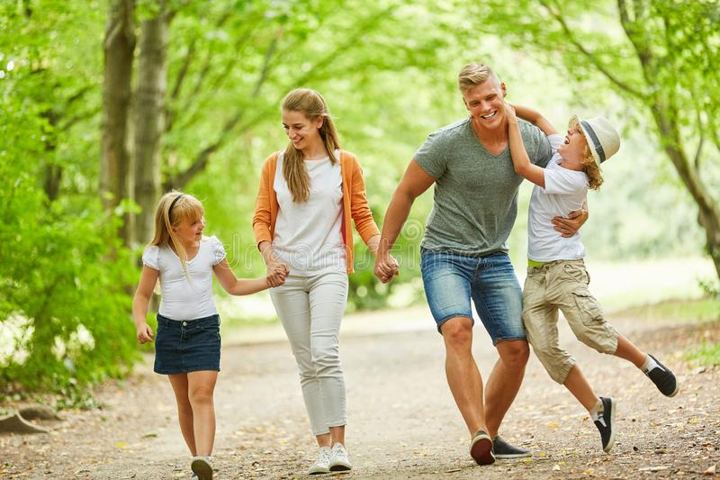 A família e as crianças vão para uma caminhada imagem de stock