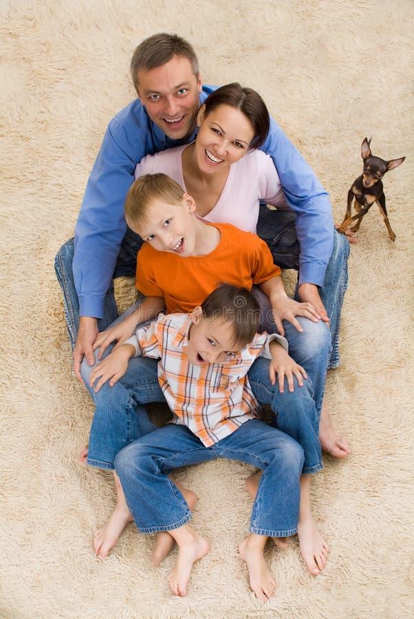 Família e cão felizes no tapete imagens de stock