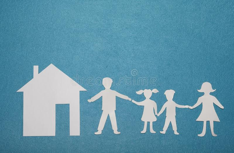 Família e casa de papel no fundo textured azul Família e conceito home Conceito do seguro fotografia de stock royalty free