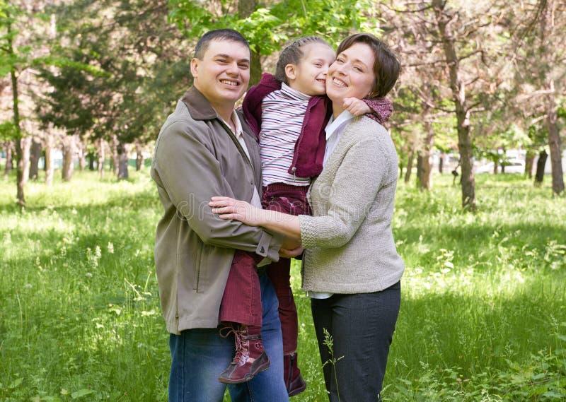 A família e a criança felizes no verão estacionam, paisagem bonita com árvores e grama verde fotos de stock royalty free