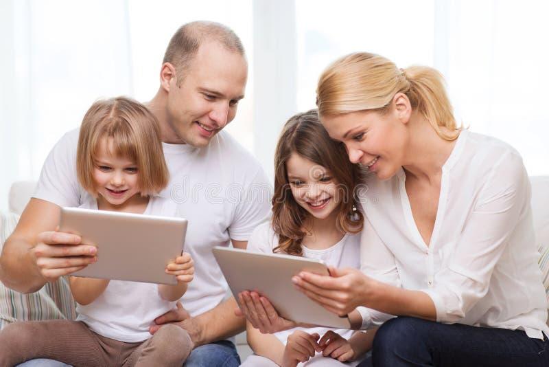Família e duas crianças com os computadores do PC da tabuleta fotografia de stock