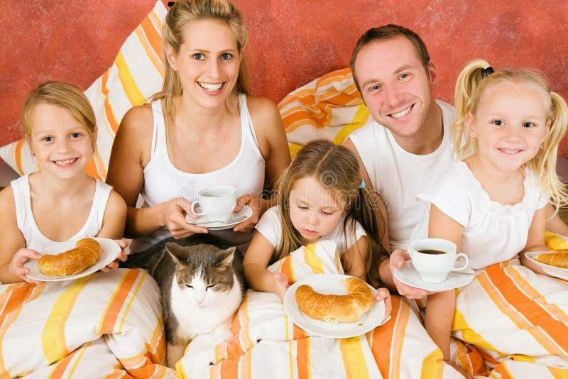 Família e gato que comem o pequeno almoço na cama foto de stock