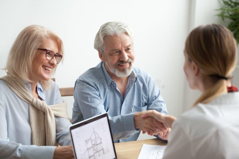 A família e o corretor de imóveis mais velhos felizes agitam as mãos que compram a casa nova imagens de stock royalty free