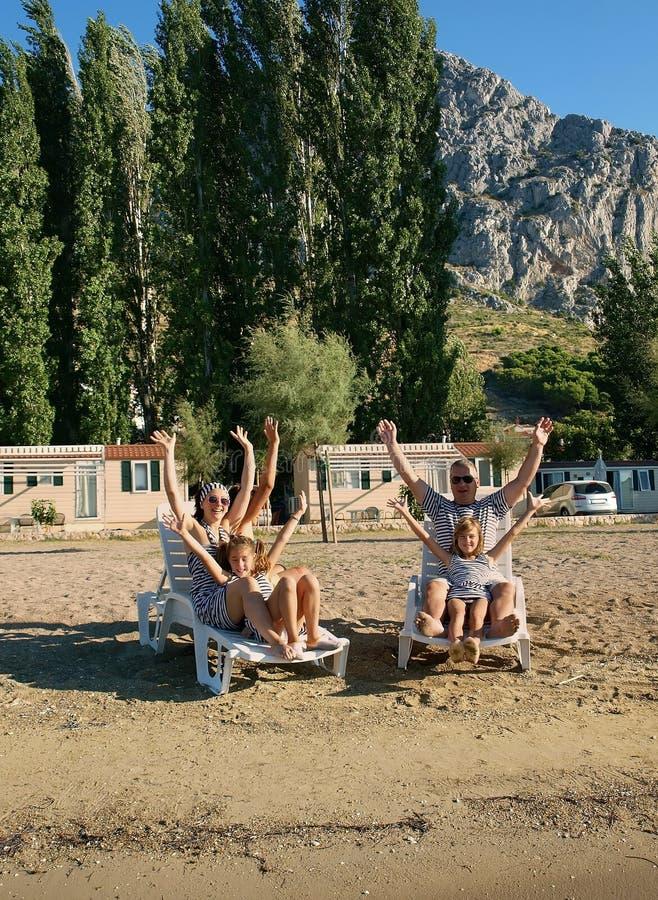 Família em cadeiras de plataforma na praia da areia imagem de stock