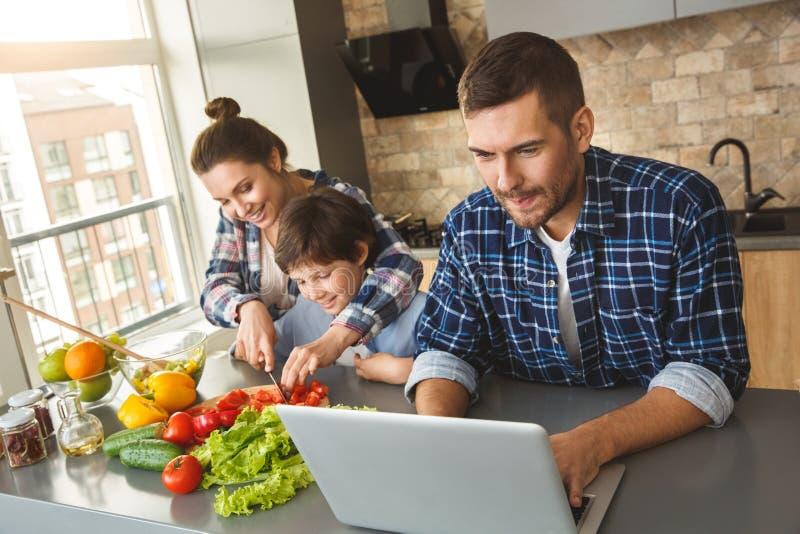 Família em casa que está na mãe da cozinha junto que corta tomates com filho quando pai que joga o jogo no portátil excitado fotos de stock