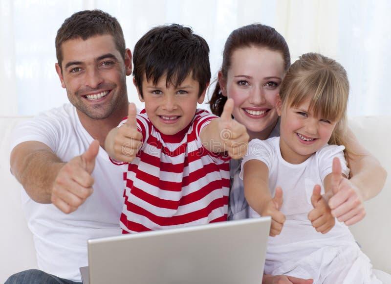 Família em casa que usa um portátil com polegares acima