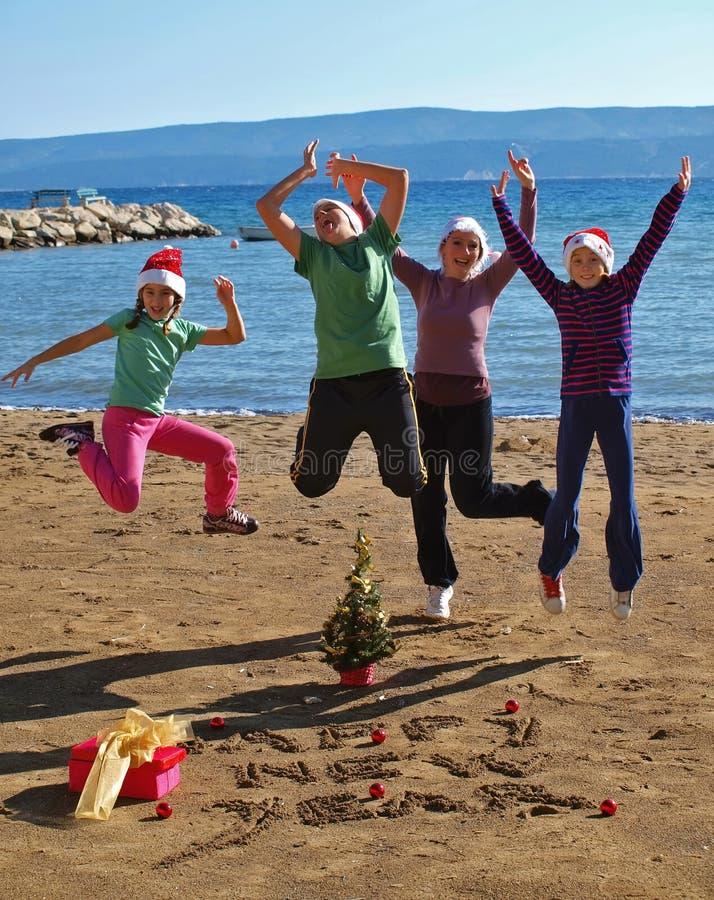 Família em comemorar o ano novo na praia da areia fotos de stock