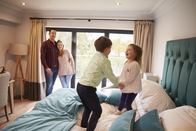 Família em férias com as crianças que jogam na cama do hotel fotos de stock