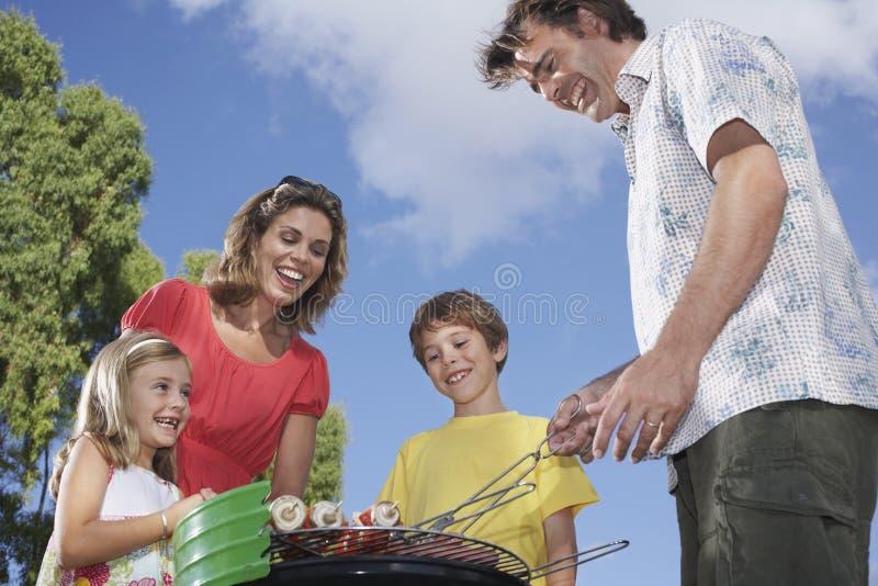 Família em torno da grade no jardim foto de stock royalty free