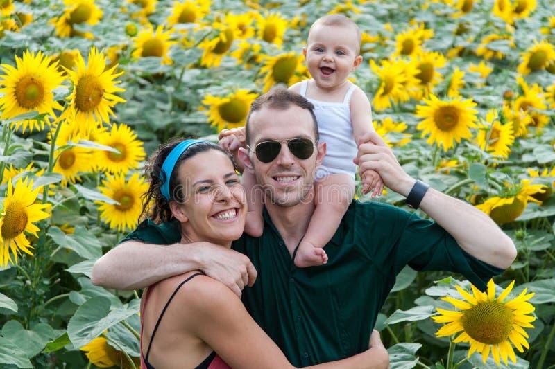 Família em um campo dos girassóis imagem de stock royalty free