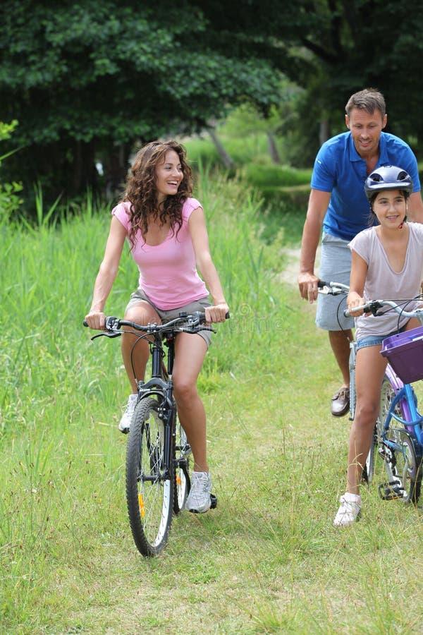 Família em um passeio da bicicleta foto de stock