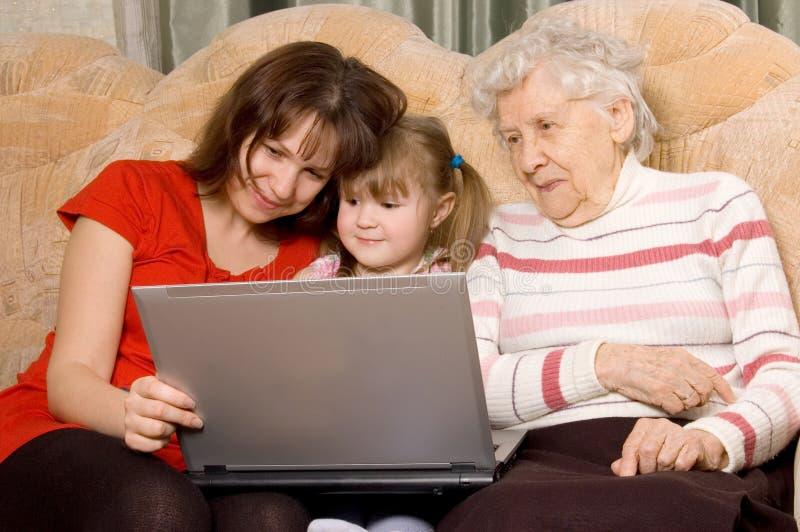 Família em um sofá com o computador imagens de stock royalty free