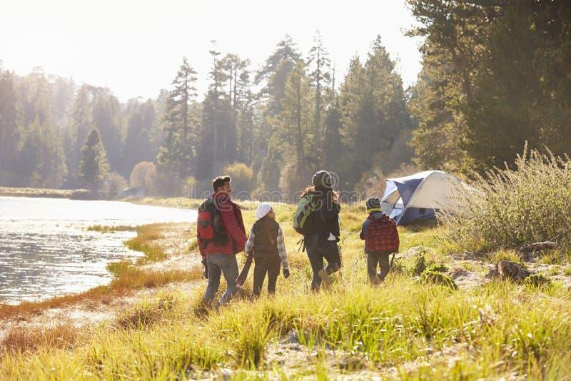 Família em uma viagem de acampamento que anda perto de um lago, vista traseira