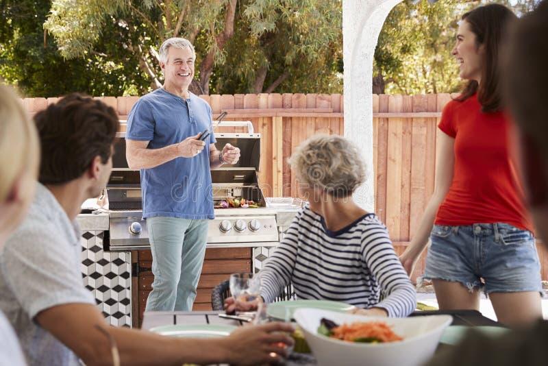 Família em uma volta do ar livre da tabela à posição do paizinho pelo assado fotos de stock