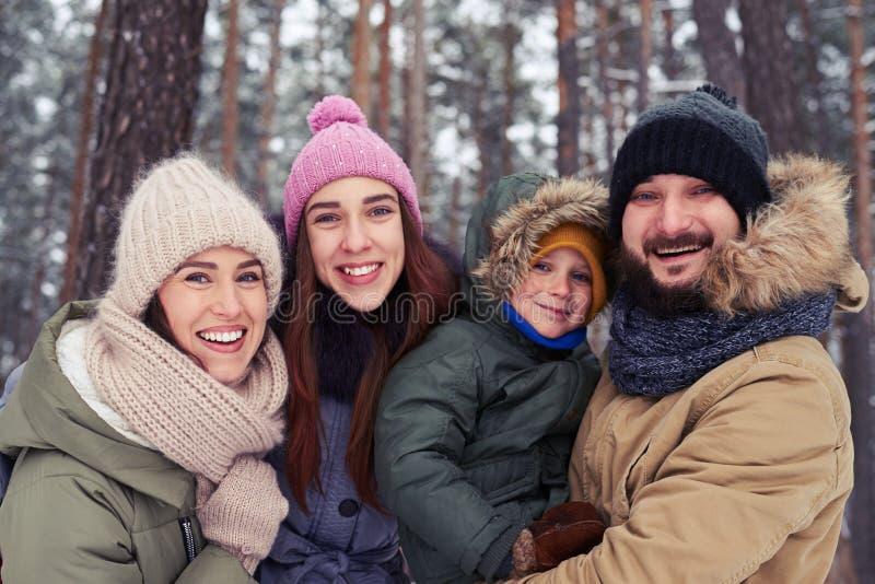 Família engraçada de 4 membros que sorriem e que riem durante o inverno foto de stock