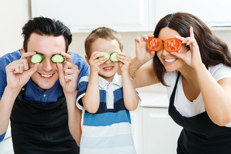 Família engraçada que joga com alimento na cozinha fotografia de stock
