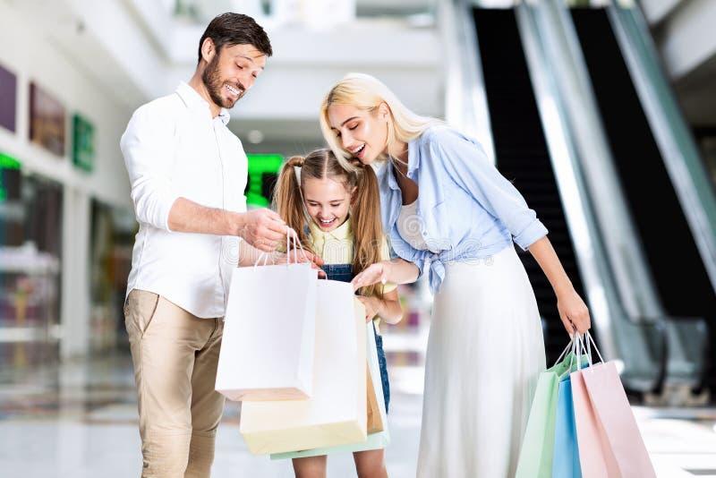 Família Entusiasmada Olhando Para As Bolsas De Compras Em Mall imagens de stock