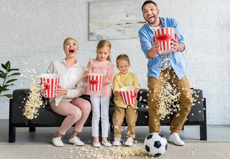 família entusiasmado com as duas crianças que guardam caixas e que jogam a pipoca imagem de stock royalty free