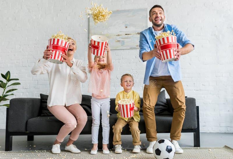 família entusiasmado que guarda caixas e que joga a pipoca fotografia de stock