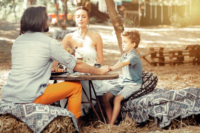 Família espiritual agradável que reza antes de sua refeição fotos de stock royalty free