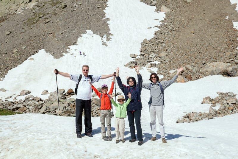 A família está ficando na neve nas montanhas foto de stock