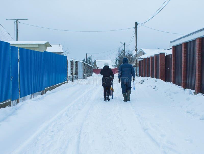 A família está na estrada na vila do inverno fotos de stock