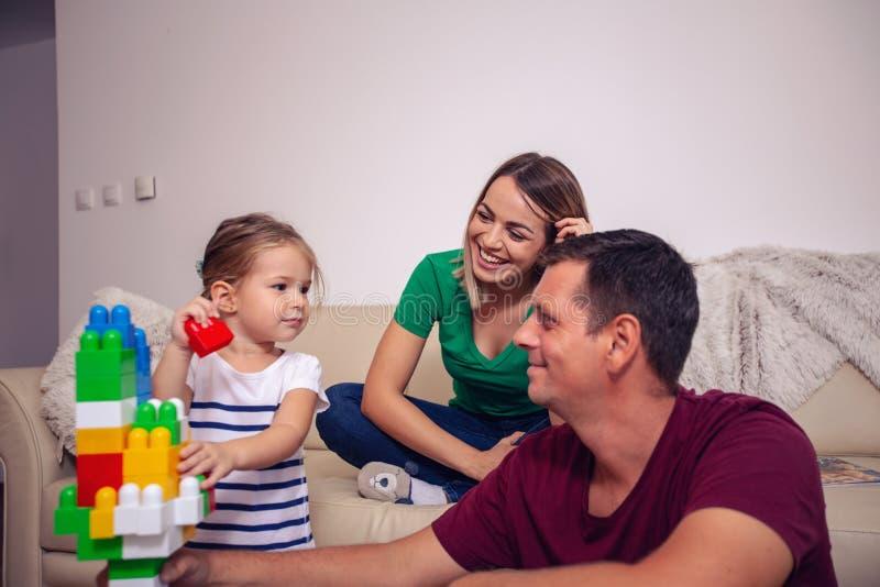 A família está tendo o divertimento que joga com filha bonito em casa foto de stock