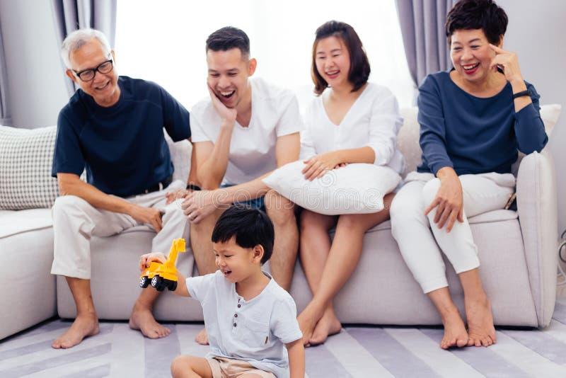 Família extensa asiática feliz que senta-se no sofá junto e na criança pequena de observação que joga o brinquedo no assoalho com imagens de stock