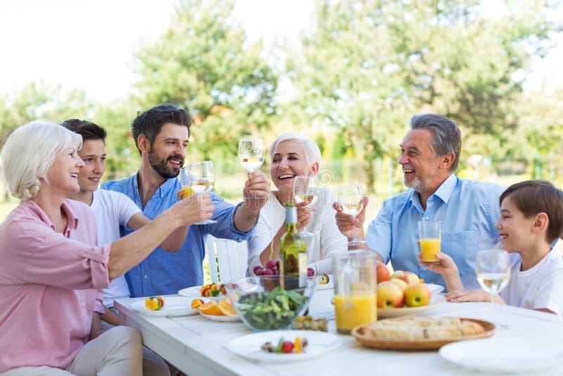 Família extensa que come fora fotografia de stock