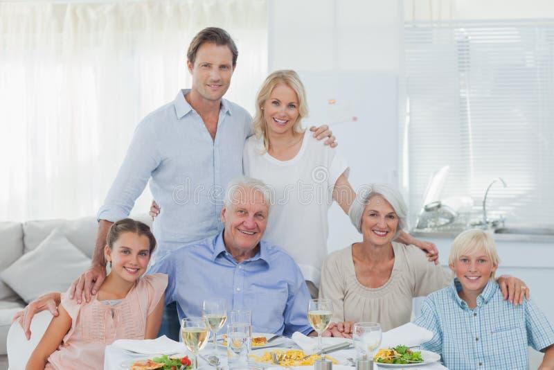 Família extensa que sorri na tabela de comensal imagens de stock