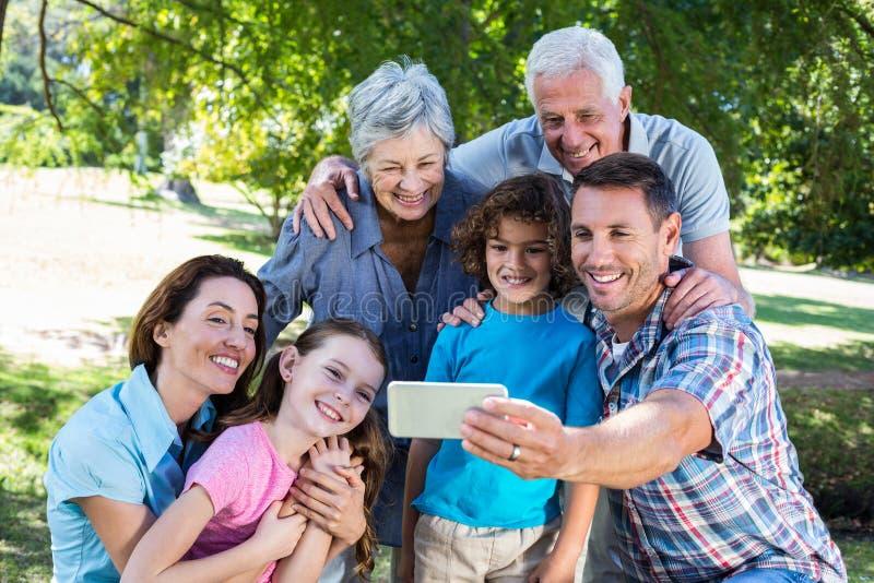 Família extensa que toma um selfie no parque imagem de stock royalty free