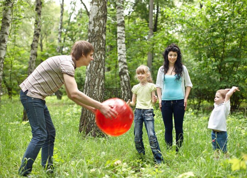 Família feliz ao ar livre que joga a esfera. fotografia de stock