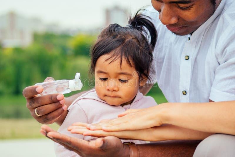 Família feliz aplicando gel antibacteriano doseador à mão fotografia de stock