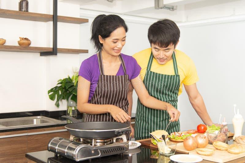 Família feliz Casal asiático adorável, mulher bonita e homem bonito preparando ingredientes e cozinhando comida para tomar café d fotografia de stock