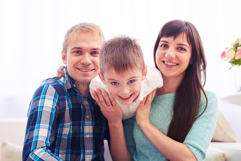 A família feliz caucasiano nova em sua sala de visitas tiver o divertimento quando imagem de stock