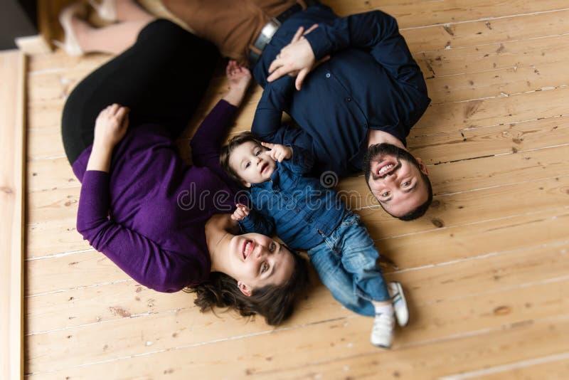 Família feliz colocada no assoalho fotos de stock