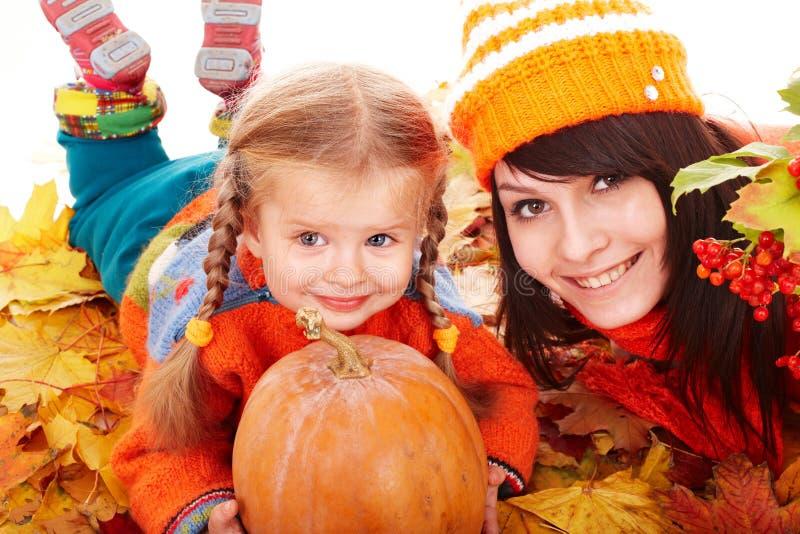 Família feliz com a abóbora nas folhas de outono. fotografia de stock