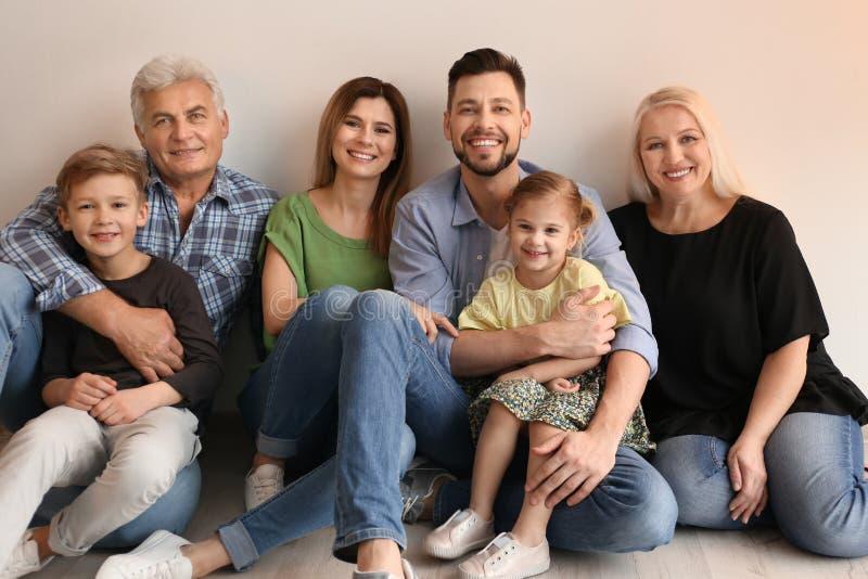 Família feliz com as crianças bonitos que sentam-se no assoalho imagem de stock