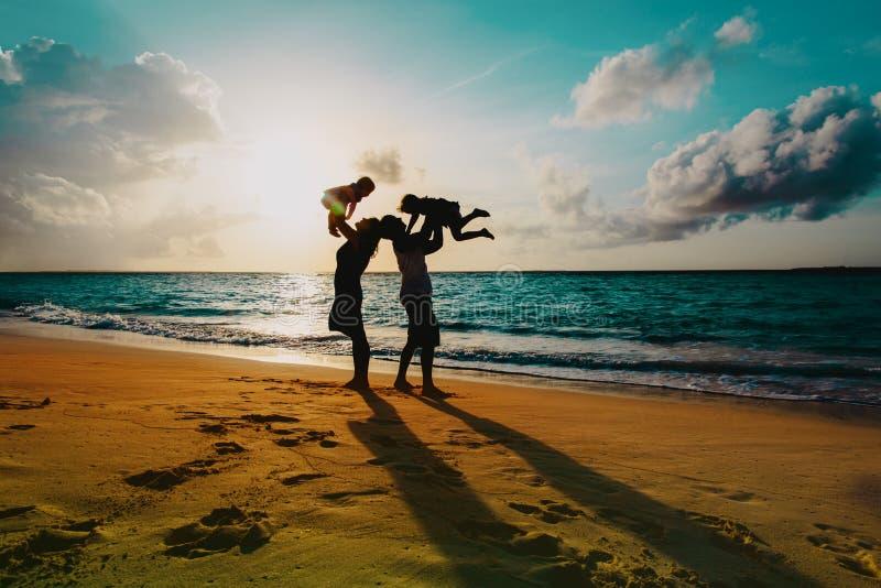 Família feliz com as crianças no jogo na praia do por do sol foto de stock royalty free