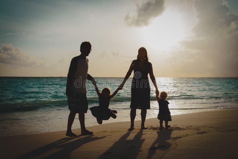 Família feliz com as crianças no jogo na praia do por do sol imagens de stock royalty free