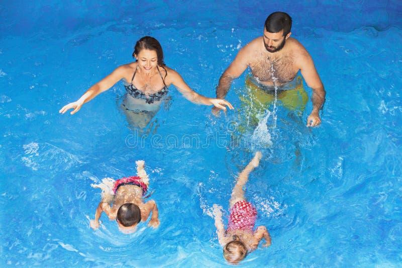 Família feliz com as crianças que nadam com divertimento na associação azul imagem de stock royalty free