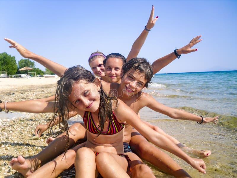 Família feliz com as crianças que têm o divertimento na praia fotografia de stock