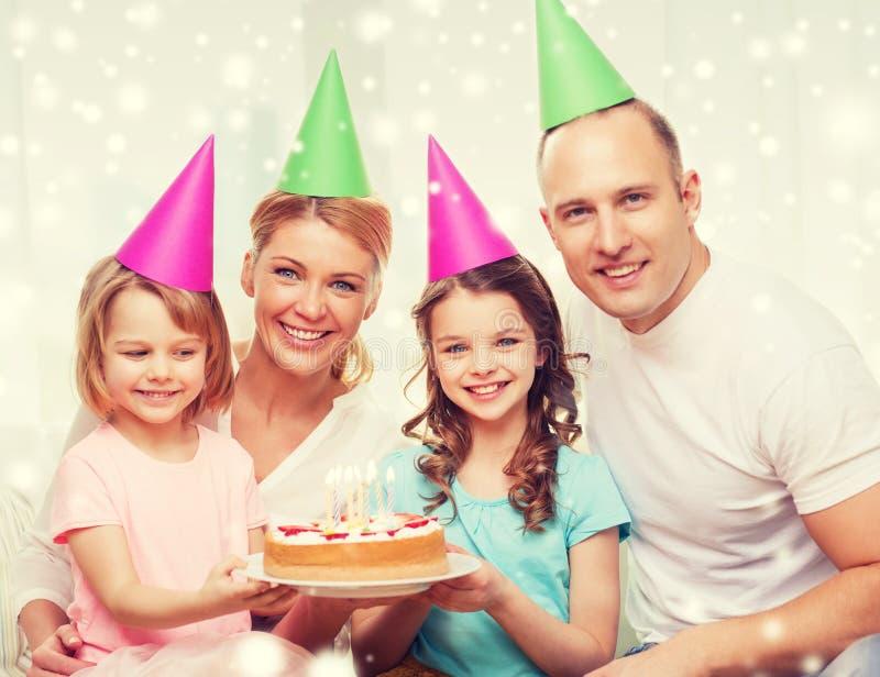 Família feliz com as duas crianças em chapéus do partido em casa imagem de stock