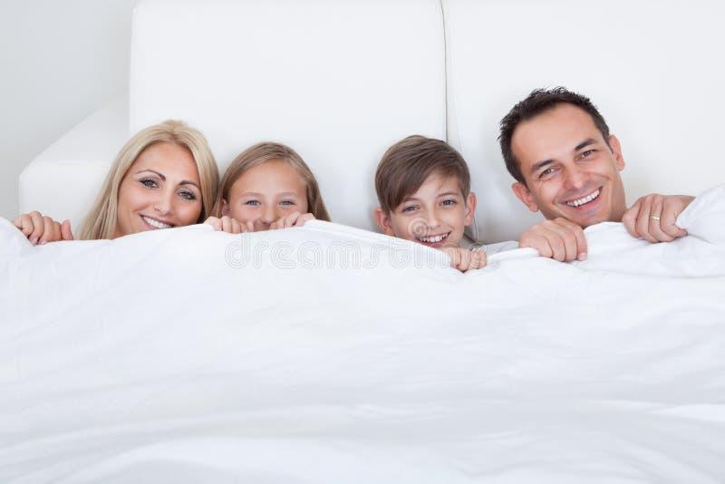 Família feliz com as duas crianças na cama sob a tampa fotografia de stock